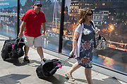 Passing a hoarding that shows the northern Embankment on the River Thames, two visitors to London each pull travel bags along York Road, SE1  on 16th July 2019, in London, England.