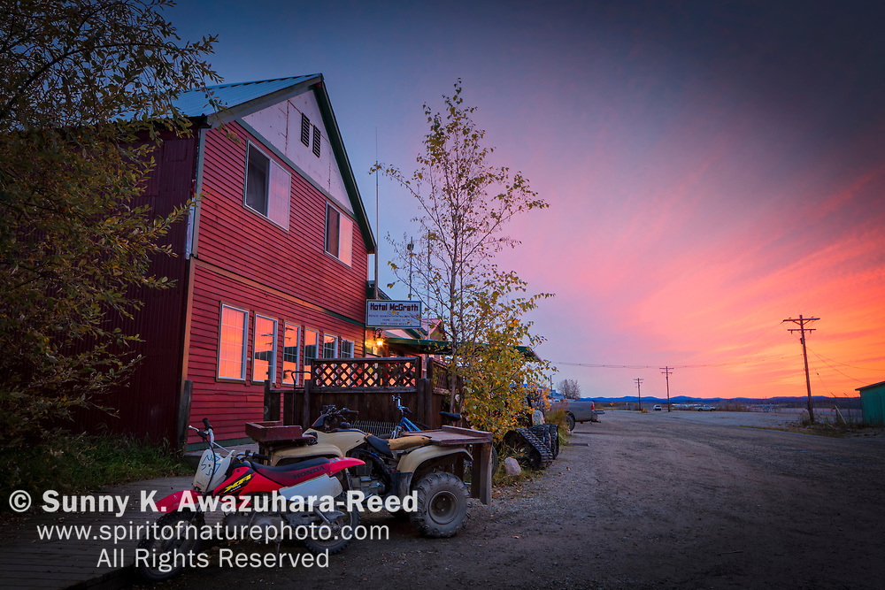 Pastel sky reflects on the window of Hotel McGrath at sunset. Four wheeler and old moter bike parked at the front. McGrath, Interior Alaska, Autumn.