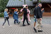 A Polish man carries pink fairground bear along Krupowki Street, on 16th September 2019, in Zakopane, Malopolska, Poland.