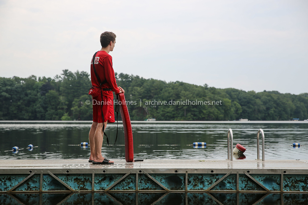 (6/29/19, FRAMINGHAM, MA) Life Guard Max Olson, of Framingham, stands on the dock at Saxonville Beach where he helps keep swimmers safe in Framingham on Saturday. [Daily News and Wicked Local Photo/Dan Holmes]
