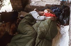 Homeless couple sleeping rough in street; in sleeping bags,