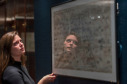"""© Licensed to London News Pictures. 03/11/2016. London, UK. A staff member inspects a rare map of ancient China at the preview of Chinese artworks entitled """"Treasures Of The Song & Qing Dynasties"""" to be auctioned at Sotheby's in November.   Photo credit : Stephen Chung/LNP"""
