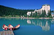 Canoes wait for tourists near the Chateau Lake Louise hotel, Lake Louise, Banff National Park, Alberta, Canada.