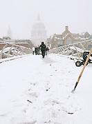 A city worker chips ice frozen to the Millenium Bridge in London, UK