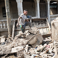 A boy walks over heaps of destroyed belongings in his neighbourhood in La Planeta.<br /> <br /> Hurricanes Eta and Iota hit hard on the north coast of Honduras, leaving some areas flooded for three weeks, destroying people's furniture, belongings, vehicles and houses as well as standing crops.