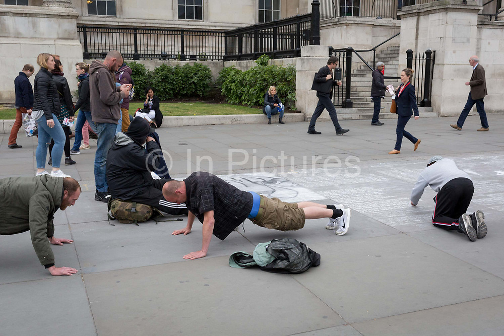 A a street artists draws on the pavement, two men try to outdo the other with press-ups on the pavement in Trafalgar Square, on 2nd May 2019, in London, England.