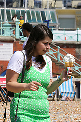 © Licensed to London News Pictures. 30/05/2021. Brighton, UK. A woman with ice-cream on the Brighton seafront on the hottest day of the year so far. According to the Met Office, a high of 24 degrees celsius is forecast for the bank holiday weekend, after weeks of rain in the South East of England. Photo credit: Dinendra Haria/LNP