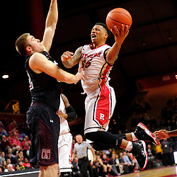 D'Von Campbell #55 of the Rutgers Scarlet Knights drives to the basket against Dalton Pepper #32 of the Temple Owls during the second half of Rutgers men's basketball vs Temple Owls in American Athletic Conference play on Jan. 1, 2014 at Rutgers Louis Brown Athletic Center in Piscataway, New Jersey.