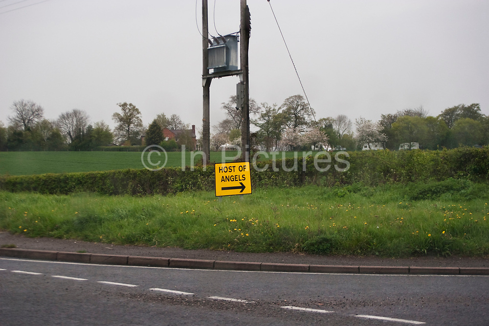 """Sign which reads 'Host of Angles"""" points into the landscape near Great Malvern in Worcestershire. Possibly a sign advertising a party."""