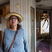 Karen Johnny in her mobile home at the JWJ Mobile Home Park in Fort Defiance, Ariz. Tuesday, August 13. Behind her you can see the bedroom where a tree fell on the trailer breaking through the roof.