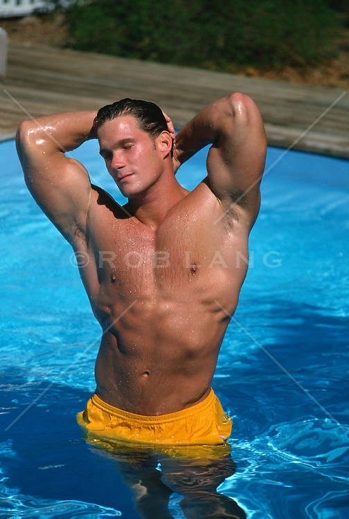 Hunky muscular man standing in a swimming pool posing in the sun