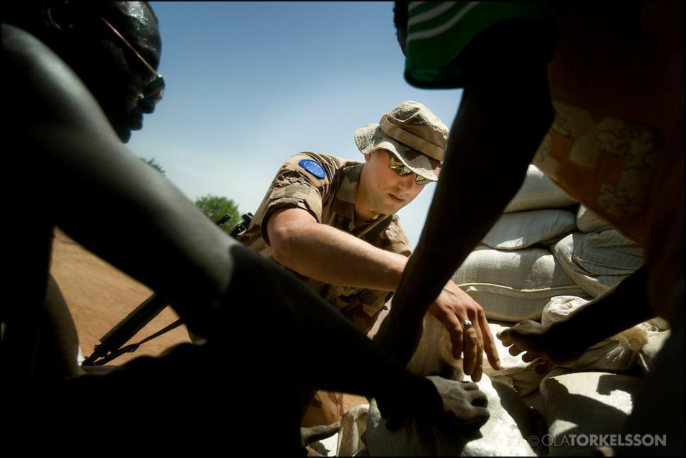 """N´Djamena (Chad) 080321 **.Bilder på svenska soldater och den gemensamma campen -""""Camp Europa"""" i N`Djamena. Svenskarna väntar på att röra sig mot Abeche..Henricsson sätter upp ettt skyttevärn med hjälp av lokalanställda. Tv Abdullah Mohamed och Muhamed Adu..Foto Ola Torkelsson .Copyright 2008 © Ola Torkelsson"""