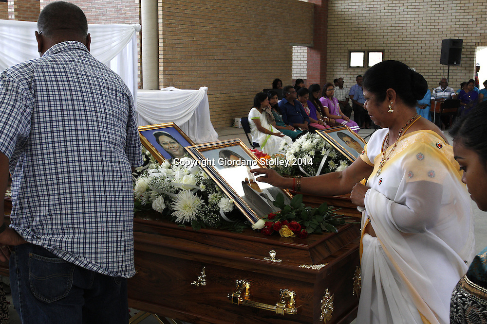 DURBAN - 4 March 2014 - A mourners touches the picture of Melarisa Kandasamy as she pays her last respects. Melarisa, her mother Mala and her brother Megandren were allegedly beaten to death in their home by her father Rajan Kandasamy, who is alleged to have used using a gada --  a traditional Indian mace carried by the Hindu god Hanuman Picture: Allied Picture Press/APP