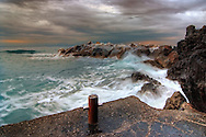 A small harbour along the rugged coast near to Riomaggiore, one of the five villages if the Cinque Terre in Liguria, Italy. Taken on a early morning on January during a strong wind storm with some rain and heavy sea.