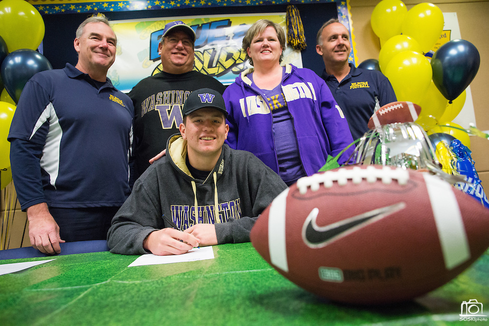 Jason Scempos, his parents, and Milpitas High School football coaches pose with a duplicate National Letter of Intent to play football at the University of Washington during the NCAA National Signing Day event at Milpitas High School in Milpitas, California, on February 4, 2015. (Stan Olszewski/SOSKIphoto)