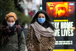 """© Licensed to London News Pictures. 12/01/2021. London, UK. Women wearing protective face coverings walk past the Government's 'Stay Home, Save Lives' Covid-19 publicity campaign poster in north London, as the number of cases of the mutated variant of the SARS-Cov-2 virus continues to spread around the country. Prime Minister Boris Johnson has said that the public should """"stay at home"""". Photo credit: Dinendra Haria/LNP"""