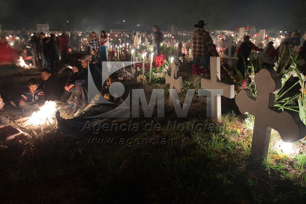 Toluca, Méx.- Miles de personas, siguiendo la tradicion ancestral del dia de muertos, velan a sus difuntos al pie de las tumbas que adornan con flores y alumbran con velas en el panteon de la comunidad Otomí de San Pablo Autocpan, a 8 kilometros al norte de la ciudad de Toluca. Agencia MVT / Mario Vazquez de la Torre. (DIGITAL)