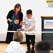 Students prepare to cut the ribbon during a ceremony in the new gymnasium at Eastwood Elementary School in Hillsboro, Ore., on Tuesday, Feb. 4, 2020.