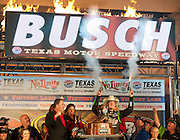Kyle Busch (18) in the Interstate Batteries Toyota shoots a pair of six-shooter as he celebrates in victory lane after winning the Sprint Cup NRA 500 at Texas Motor Speedway in Fort Worth on Saturday, April 13, 2013. (Cooper Neill/The Dallas Morning News)