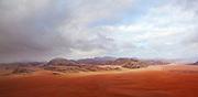 A vast red sand desert extends to eroded sandstone mountains in Wadi Rum, Jordan.