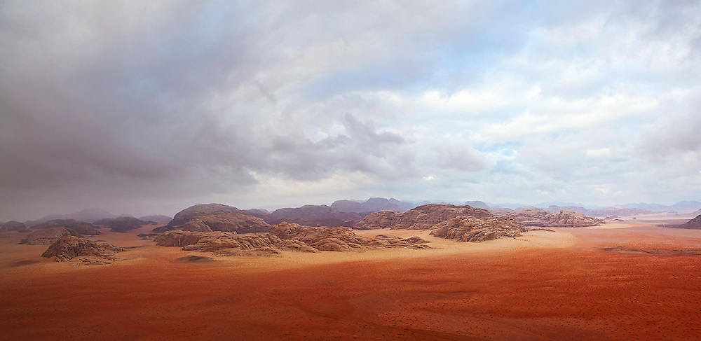 A vast red sand desert extends to eroded sandstone mountains in Wadi Rum, Jordan.