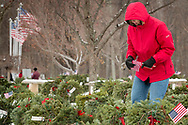 Goshen, New York - A woman carries American flags during a Wreaths Across America ceremony at Orange County Veterans Memorial Cemetery on Dec. 16, 2017. About 3,000 wreaths were placed at graves, and small American flags were added to the wreaths at veterans' graves.