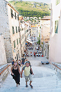 View of the Uz Jezuite stairs down to the city and the Gunduliceva Poljana Square. People walking up the steep stairs. Restaurant tables on the square in the background. Dubrovnik, old city. Dalmatian Coast, Croatia, Europe.