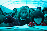 School under a blue tarp at the camp for displaced Syrians in Atmeh, Syria. From left to right is Miriam Boustan (10), Rahaf el Saleh (10), and Sajeda el Khalaf (6).