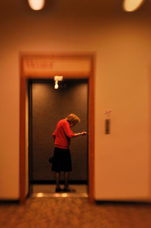 An elderly woman steps into an elevator.