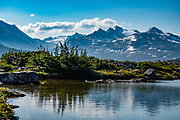 A pond at White Pass reflects mountains of the Boundary Ranges of the Coast Mountains, at Outhouse Hill Pullout on South Klondike Highway, British Columbia, Canada. The White Pass Trail (or Dead Horse Trail) was one of the two main passes used by prospectors during the Klondike Gold Rush. It leads from Skagway, Alaska, to the chain of lakes at the headwaters of the Yukon River: Crater Lake, Lake Lindeman, and Bennett Lake. Skagway was founded in 1897 on the Alaska Panhandle. The 98-mile/158-km South Klondike Highway (Skagway-Carcross Road) connects Skagway over White Pass via British Columbia to the Alaska Highway, in the Yukon southeast of Whitehorse.