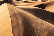 Wind blows sand into the air at the sand dunes of Erg Lihoudi, Morocco.
