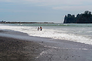 A father and son play in the water at Rialto Beach, Olympic National Park, Washington, USA.