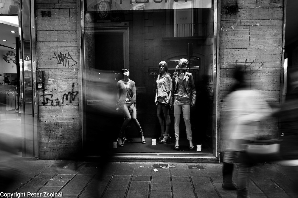 Pedestrians walking before a shop in the streets of Naples, Italy