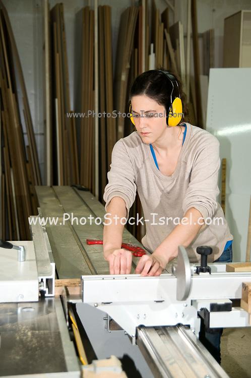 Female carpenter uses a power saw to cut oak wood