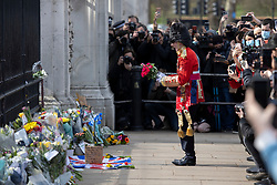 © Licensed to London News Pictures.09/04/2021. London, UK. A man dressed as member of the Coldstream Guards places flowers in front of Buckingham Palace following an announcement regarding the death of Prince Philip. Buckingham Palace has announced that Prince Philip The Duke of Edinburgh passed away this morning at Windsor Castle . Photo credit: George Cracknell Wright/LNP