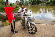 28 OCTOBER 2012 - SUNGAI KOLOK, NARATHIWAT, THAILAND:  A man and his son sit on a motocycle and wait to cross the border to Malaysia from Sungai Kolok,  Thailand. More than 5,000 people have been killed and over 9,000 hurt in more than 11,000 incidents, or about 3.5 a day, in Thailand's three southernmost provinces and four districts of Songkhla since the insurgent violence erupted in January 2004, according to Deep South Watch, an independent research organization that monitors violence in Thailand's deep south region that borders Malaysia.   PHOTO BY JACK KURTZ