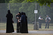 Muslim ladies with UK Met police officers who guard a temporary perimeter fence encircling Winfield House, the official residence of the US Ambassador during the visit to the UK of US President, Donald Trump, on 12th July 2018, in Regent's Park, London, England.