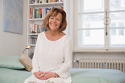 Senior woman sitting on bed and smiling, Munich, Bavaria, Germany