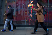 Pre-Christmas shoppers walk past a video ad loop for theLondon retailer 'Reserved', on Oxford Street, on 22nd November 2017, in London England.