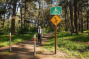 USA, Oregon, Salem, Bush Pasture Park, sign warning hikers that nesting owl may harass them and hiker looking for the owls. MR