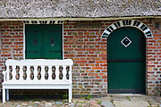 Traditional and quaint thatched cottage house and white bench on Fano Island - Fanoe - South Jutland, Denmark