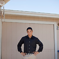 Luis De La Cruz stands in front of the garage that had neither insulation nor air conditioning in the desert near Phoenix, Arizona where he lived as an undocumented immigrant while supporting his brother and finishing high school after his mother abandoned him and his father was deported back to Mexico. Luis is now an honors student at Arizona State University, interned with an Arizona Senator in Washington and has met President Obama.