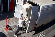 Two men tilt a tall used freezer-type eletrical device into the back of a white van on the Walworth Road in south London, on 21st September 2021, in London, England.