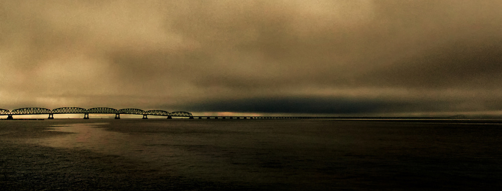 Bridging Time: A visual sense of time is set with this grainy, yellow hued photograph of the Astoria–Megler Bridge as it spans the Columbia River, making its way towards Astoria Oregon, USA.