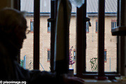 An elderly prisoner looks out of his cell window. 89 year old Fred is one of the many OAP's in prison. HMP & YOI Littlehey. Littlehey is a purpose build category C prison.