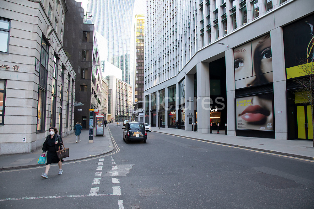 At rush hour a figure walks past a giant face wearing a face mask in the in the City of London financial district, which is virtually deserted due to the Coronavirus outbreak on 23rd March 2020 in London, England, United Kingdom. Following government advice city workers are staying at home to work leaving the streets quiet, empty and eerie. Coronavirus or Covid-19 is a new respiratory illness that has not previously been seen in humans. While much or Europe has been placed into lockdown, the UK government has announced more stringent rules as part of their long term strategy, and in particular social distancing.