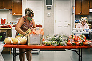 """16 SEPTEMBER 2020 - MITCHELLVILLE, IOWA: JOAN ALLSUT picks up food for a family she is helping in the pantry at the Heritage Word of Life Church. There is no grocery store in Mitchellville, a small community in eastern Polk County. It doesn't qualify as a """"food desert"""" under USDA guidelines because there are grocery stores within 10 miles in neighboring communities, but based on state data, Mitchellville is the poorest community in Polk County (which includes the Des Moines metropolitan area). The Mitchellville zip code has the lowest per capita income in Polk County. Many people don't own cars and can't get to neighboring communities to buy groceries. Every day someone from the Mitchellville library picks up hot meals from a nearby town and distributes them in the library. Heritage Word of Life, a church across the street from Library, has a food pantry in their Fellowship Room where people can pick up fresh vegetables, staples, and hygiene needs.      PHOTO BY JACK KURTZ"""