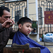 A young boy receives a hair cut on a street corner of the old quarter of Hanoi, Vietnam. Hanoi is the capital of Vietnam and the country's second largest city. Hanoi, Vietnam. 17th March 2012. Photo Tim Clayton