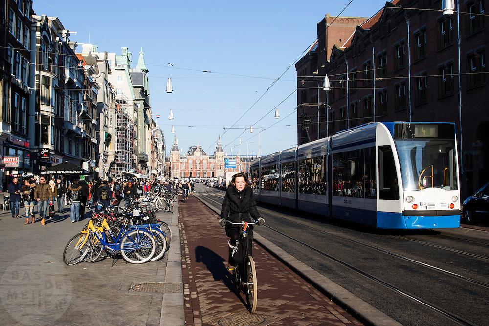 In Amsterdam fietst een vrouw over het fietspad op het Damrak, een tram rijdt over de trambaan. Het Damrak is onlangs opnieuw ingericht met een duidelijkere scheiding tussen fietsers, trams en auto's.<br /> <br /> In Amsterdam a woman rides on the bike lane on the Damrak, a tram is passing by. The Damrak is newly redesigned with a clearer separation between cyclists, trams and cars.