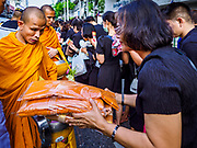 13 OCTOBER - BANGKOK, THAILAND: A woman presents a new set of monk's robes to a monk during a merit making on the first anniversary of the death of Bhumibol Adulyadej, the Late King of Thailand. About 199 monks from 14 Buddhist temples in Bangkok participated in the mass merit making at Siriraj Hospital to mark the anniversary of the revered King's death. He will be cremated on 26 October 2017.  PHOTO BY JACK KURTZ